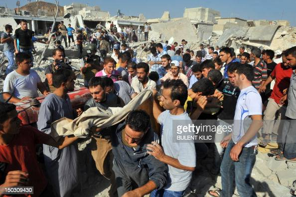 Syrians carry the body of a woman after an air strike in the town of Azaz near the northern restive Syrian city of Aleppo on August 15 2012 UN...