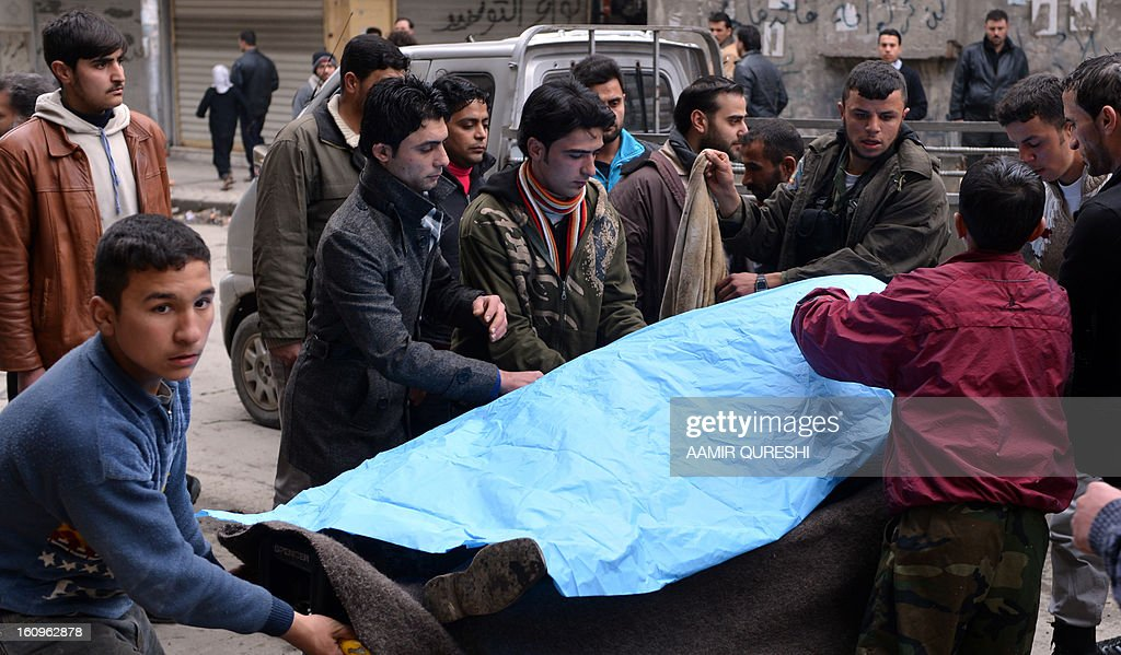 Syrians carry the body of a wounded civilian to a hospital in the northern city of Aleppo following shelling by government forces on February 8, 2013. Syrian forces shelled rebel belts, the Syrian Observatory for Human Rights said, as an army offensive raged into a third straight day.