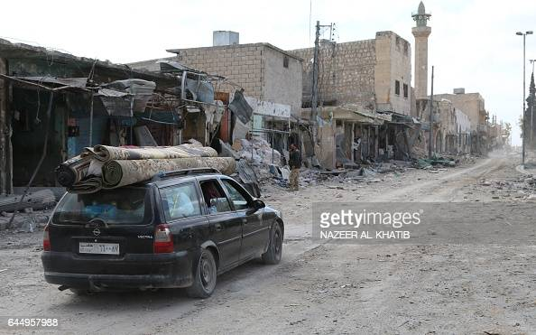 Syrians carry their belongings on top of a car in the northwestern border town of alBab on February 24 2017 as they return to their houses after...