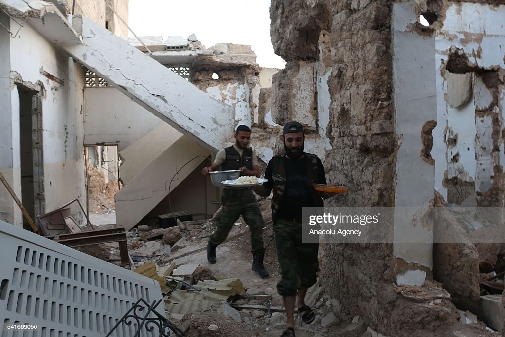 Syrians carry their foods for Iftar between wreckages of buildings during the Islamic holy month of Ramadan at Cobar district of eastern Goutha...