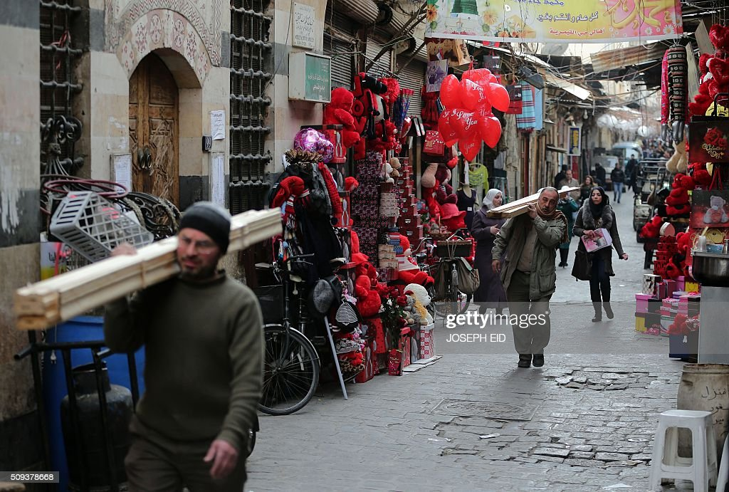 Syrians carry wood past shops displaying red teddy bears and balloons for Valentine's day in Damascus on February 10, 2016. / AFP / JOSEPH EID