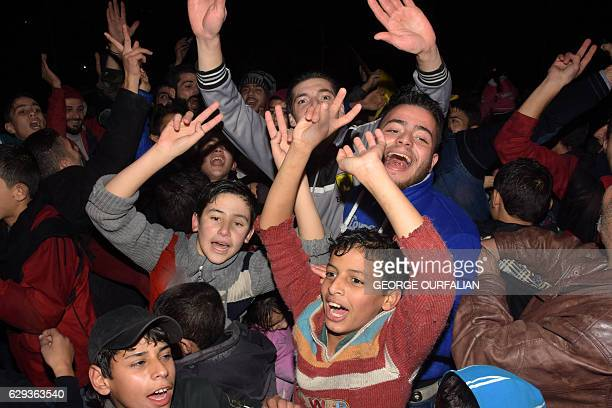 TOPSHOT Syrians celebrate on December 12 2016 in the governmentheld Mogambo neighbourhood of the northern Syrian city of Aleppo after rebel fighters...