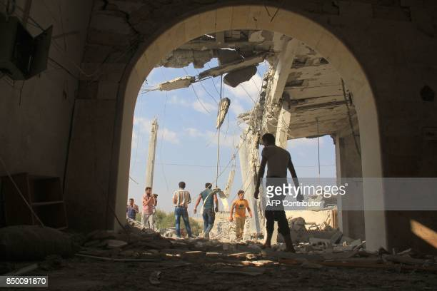 Syrians check the damage in a mosque following a reported air strike on the village of Jarjanaz in the Maaret alNuman district of Syria's Idlib...