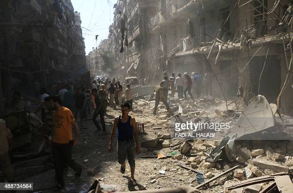 Syrians check the rubble following an air strike by government forces on the eastern Shaar neighbourhood of the northern Syrian city of Aleppo on...