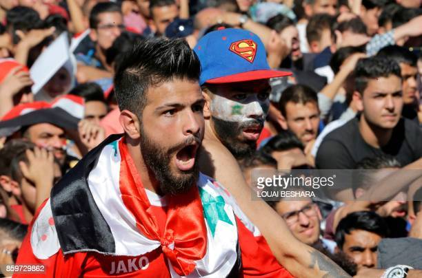 Syrians cheer on their national team at the Umayyad Square in Damascus as they watch a live broadcast of the World Cup 2018 qualifying playoff...