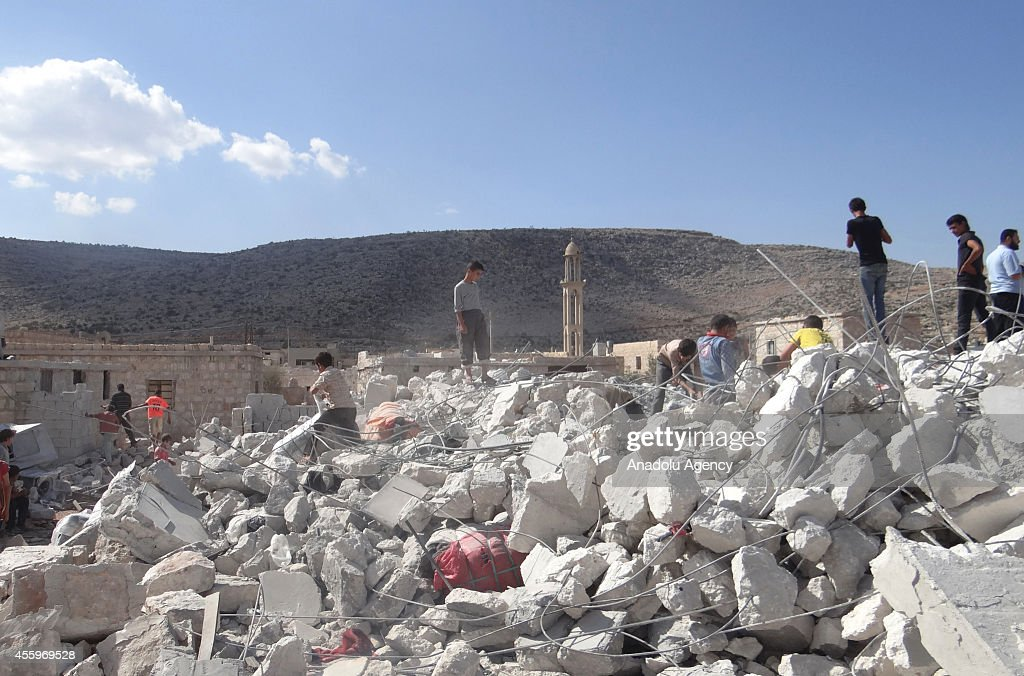 Syrians collect their belongings from the rubble of destroyed houses following the USled coalition's airstrikes against the Islamic State of Iraq and...