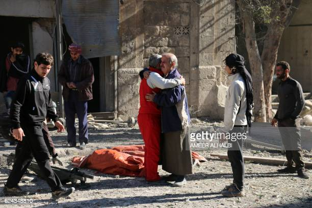 TOPSHOT Syrians comfort each other on November 19 2016 following a reported air strike on Aleppo's rebelheld neighbourhood of Bab alNayrab Intense...