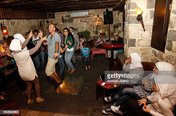 Syrians dance at a karaoke bar in Damascus on September 13 2013 When night falls in Damascus gaggles of determined revellers still head out on the...