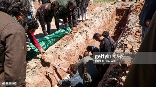 Syrians dig a grave to bury the bodies of victims of a a suspected toxic gas attack in Khan Sheikhun a nearby rebelheld town in Syrias northwestern...