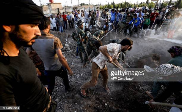 Syrians dig graves and mourn at a funeral for Arab fighters from the Kurdish People's Protection Units who were killed during the battle for the...