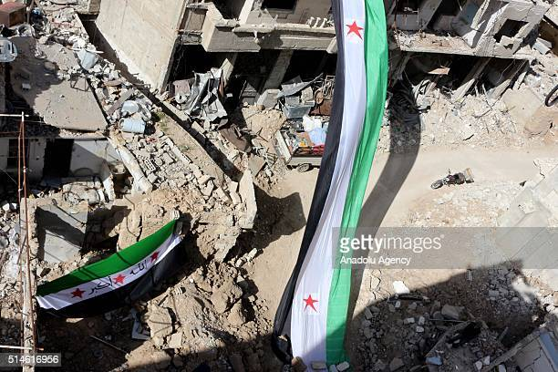 Syrians display a flag as they protest against Assad Regime in opposition controlled Jobar District of Damascus Syria on March 10 2016