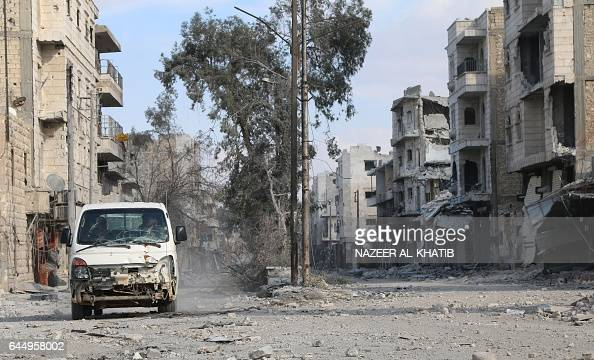 Syrians drive a damaged vehicle in the northwestern border town of alBab on February 24 2017 as they return to their houses after Turkishbacked...