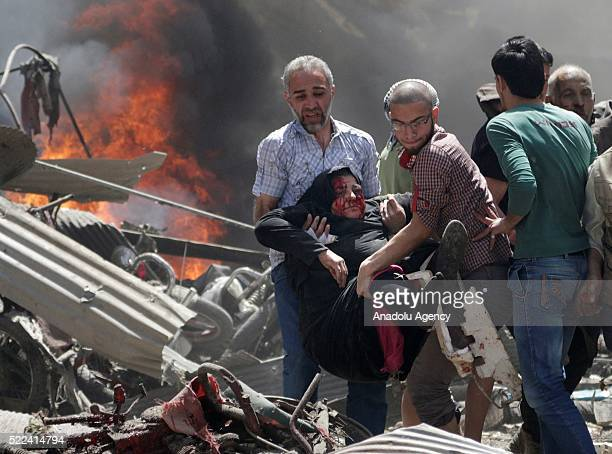 Syrians evacuate a wounded woman from the site after warcrafts belonging to Syrian army bombed a bazaar in Maarrat alNu'man south of Idlib Syria on...