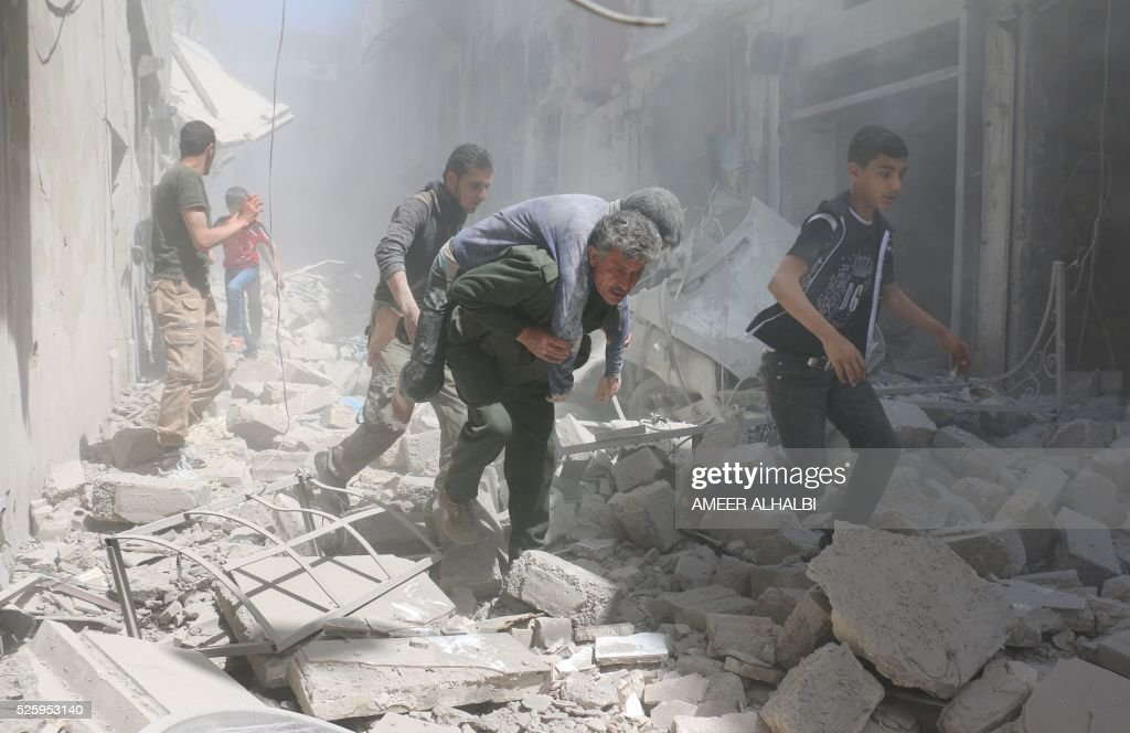 Syrians evacuate an injured man amid the rubble of destroyed buildings following a reported air strike on the rebel-held neighbourhood of Al-Qatarji, in the northern Syrian city of Aleppo, on April 29, 2016. Fresh bombardment shook Syria's second city Aleppo, severely damaging a local clinic as outrage grows over an earlier air strike that destroyed a hospital. The northern city has been battered by a week of air strikes, rocket fire, and shelling, leaving more than 200 civilians dead across the metropolis. The renewed violence has all but collapsed a fragile ceasefire deal that had brought an unprecedented lull in fighting since February 27. / AFP / AMEER