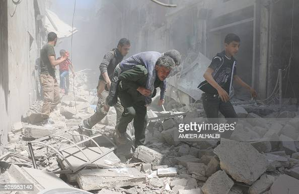 TOPSHOT Syrians evacuate an injured man amid the rubble of destroyed buildings following a reported air strike on the rebelheld neighbourhood of...