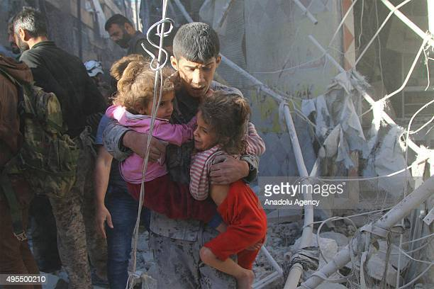 Syrians evacuate people from damaged buildings following the Russian airstrikes on the oppositioncontrolled Mashhad neighborhood of Aleppo Syria on...