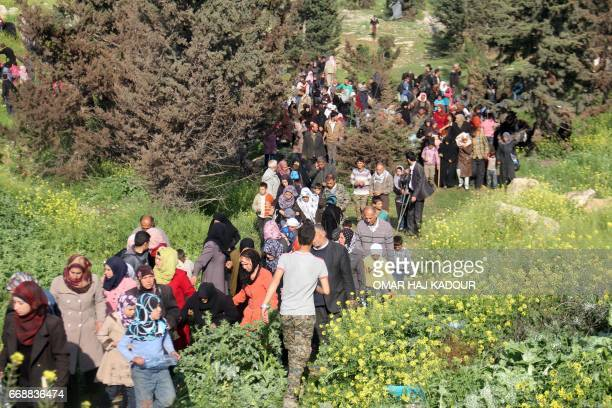 Syrians evacuated from two besieged governmentheld towns of Fuaa and Kafraya flee into a field near the site of a suicide car bombing that targeted...