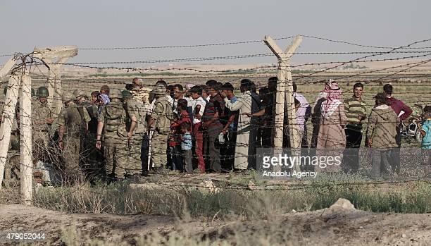 Syrians fled from clashes in Tell Abyad region of Syria wait after they cross Turkish Syrian border to take shelter in Turkey on June 30 2015 in...