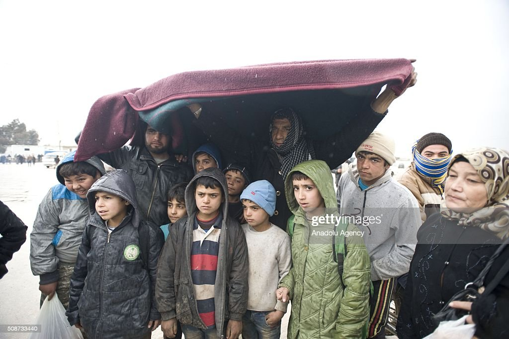 Syrians, fled from their homes due to Russian and Assad Regime forces attacks, walk along the way between Aleppo and Azez to arrive Turkish border in Syria on February 6, 2016.