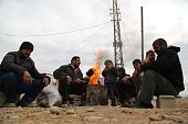 Syrians fled with their family of eight from attacks of Islamic State of Iraq and Levant from Syrian city of Hama is seen around a burning fire set...