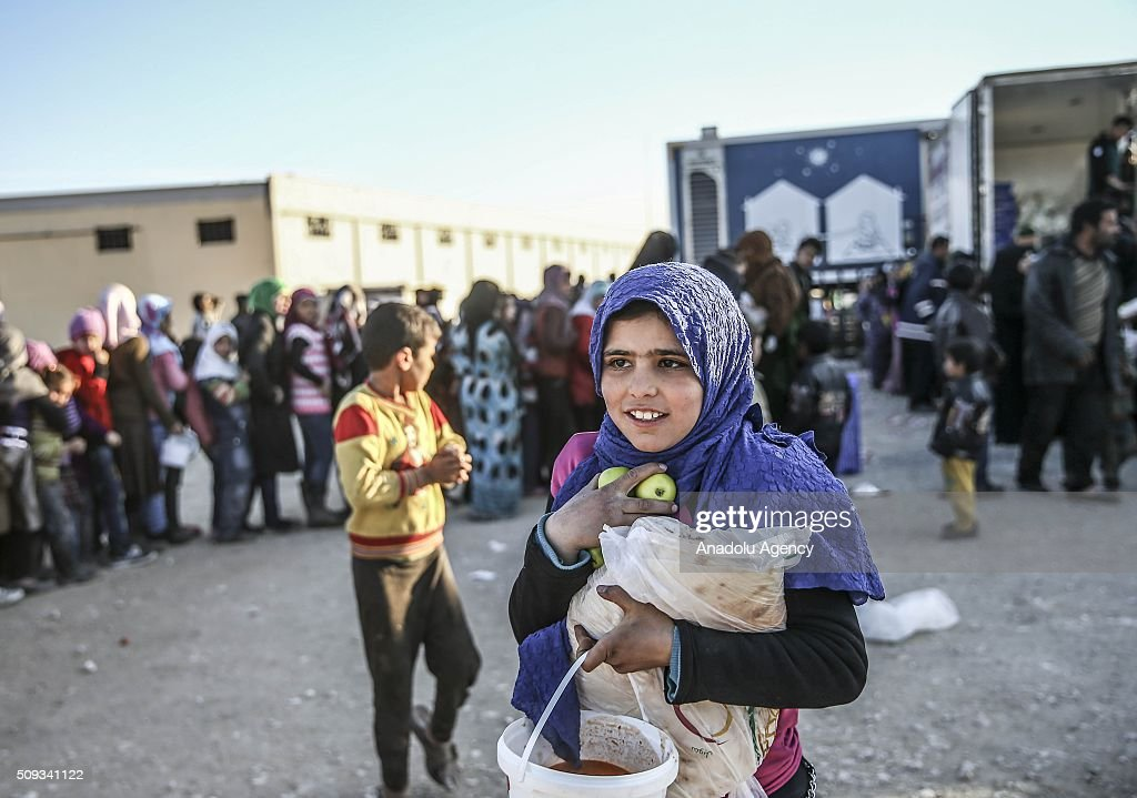Syrians, flee the attacks of Syrian and Russian air forces wait in a queue to receive food, distributed by a Turkish NGO IHH Humanitarian Relief Foundation, as they shelter at tents and try to live their lives with humanitarian aid send by Turkey, UNHCR and other Turkish Humanitarian aid organizations, close to the Bab al-Salameh border crossing on Turkish-Syrian border near Azaz town of Aleppo, Syria on February 10, 2016.