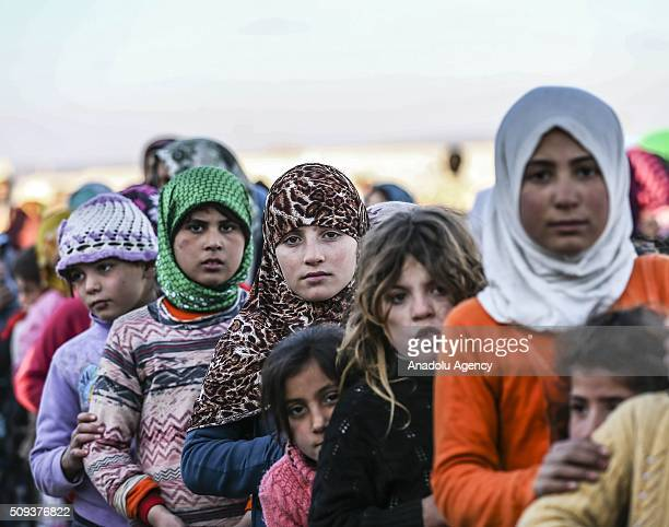 Syrians flee the attacks of Syrian and Russian air forces wait in a queue to receive food distributed by a Turkish NGO IHH Humanitarian Relief...