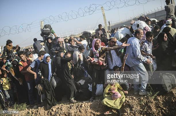 Syrians fleeing the war pass through broken border fences and trenches to enter Turkish territory illegally near the Turkish border crossing at...