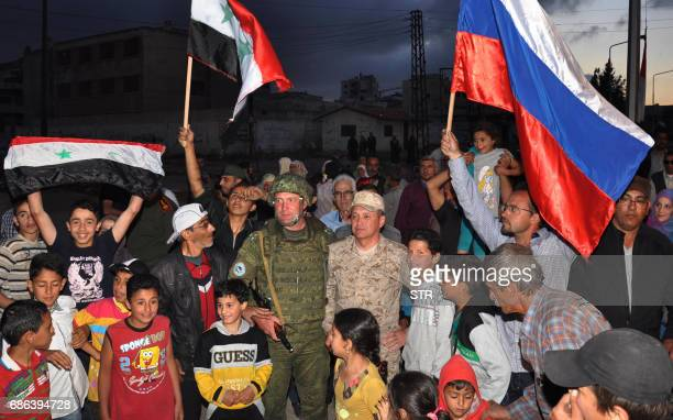 Syrians gather around a Russian soldier as opposition fighters and their families prepare to be evacuated from the Waer neighbourhood the last...