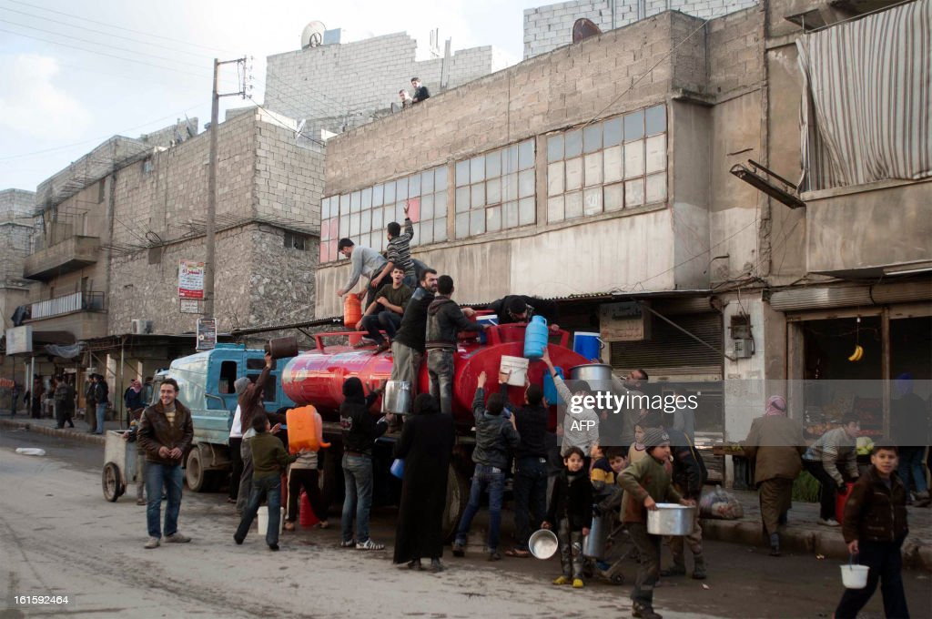 Syrians gather around a water truck in Karm al-Myessar neighborhood of Aleppo, on February 12, 2013. The death toll from the Syria civil war is nearing 70,000, UN rights chief Navi Pillay said as she again condemned the UN Security Council's failure to agree action on the conflict.