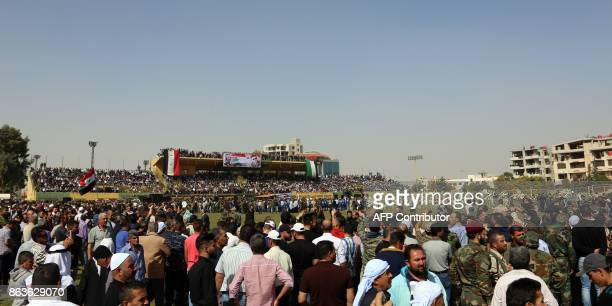 Syrians gather at a stadium to attend the funeral of Brigadier General Issam Zahreddine in the southern city of Suwaida on October 20 with a banner...