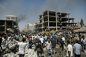Syrians gather at the site of a bomb attack in Syria's northeastern city of Qamishli on July 27 2016 A double bomb attack killed at least 14 people...