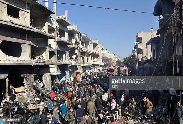 Syrians gather at the site of a car bomb explosion in alZahra neighborhood in Homs on December 12 2015 Fifteen civilians were killed and dozens more...