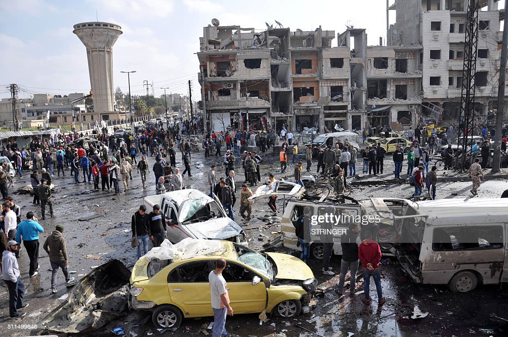 Syrians gather at the site of a double car bomb attack in the AlZahraa neighbourhood of the central Syrian city of Homs on February 21 2016 Homs city...