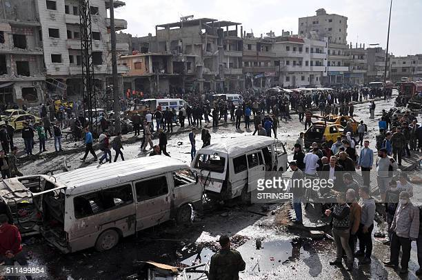 TOPSHOT Syrians gather at the site of a double car bomb attack in the AlZahraa neighbourhood of the central Syrian city of Homs on February 21 2016...