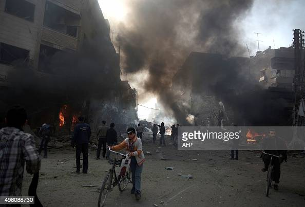 Syrians gather at the site of a reported air strike by government forces in the rebelheld area of Douma east of the capital Damascus on November 7...
