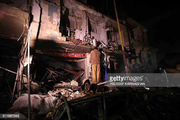 Syrians gather at the site of a series of attacks the area of the Sayyida Zeinab shrine south of Syria's capital Damascus on February 21 2016 At...