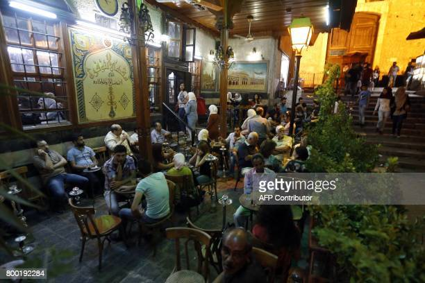 Syrians gather in a Damascus coffeehouse on June 19 2017 With a slender sword in one hand and an antique storybook in the other Ahmad alLahham...