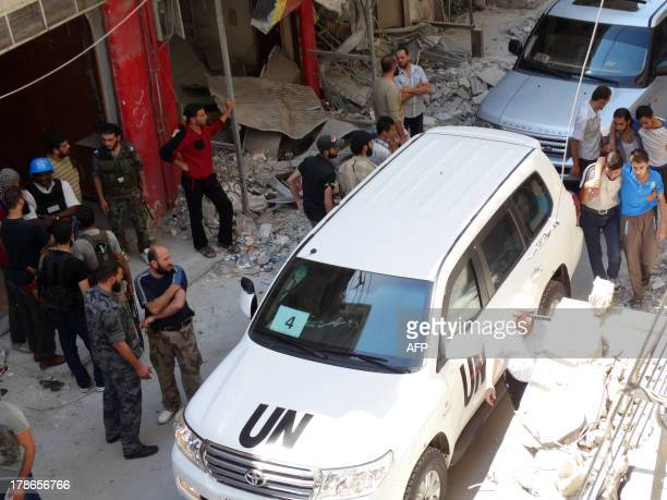Syrians gather near a vehicle of the United Nations arms experts as they inspect a site suspected of being hit by a deadly chemical weapons attack...