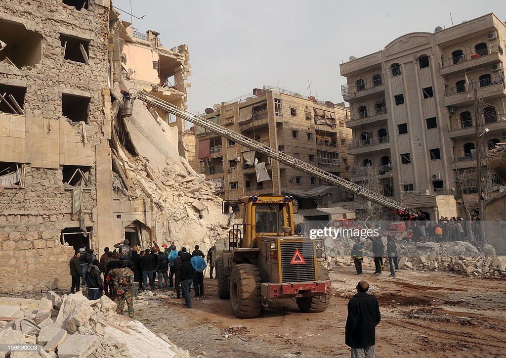 Syrians gather next to the scene of an explosion in Aleppo on January 18, 2013. A Belgian-born French journalist, Yves Debay, died from sniper fire in the north Syrian city, the Syrian Observatory for Human Rights said.