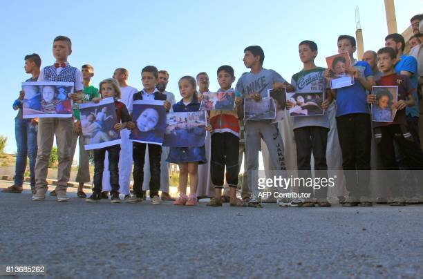 Syrians gather on July 12 2017 with pictures of victims during a memorial in Khan Sheikhun a rebelheld town in the northwestern Syrian Idlib province...