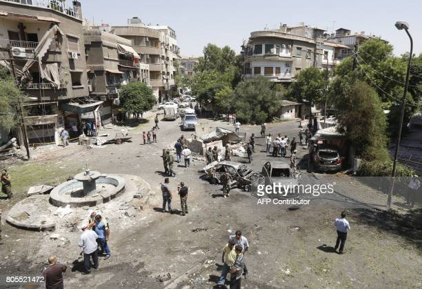 Syrians gather to inspect the damage at the site of a suicide bomb attack in the capital Damascus' eastern Tahrir Square district on July 2 2017...