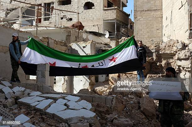 Syrians hold a flag as they protest against Assad Regime in opposition controlled Jobar District of Damascus Syria on March 10 2016