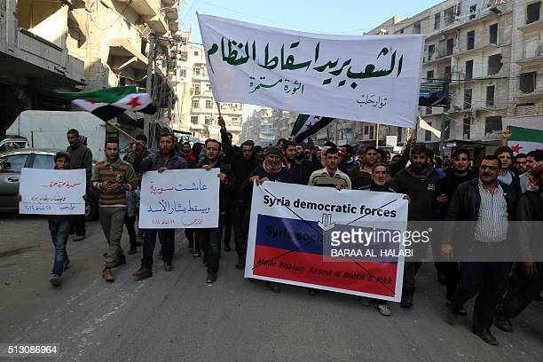 Syrians hold banners during a demonstration against the Syrian regime on February 29 2016 in the rebel held alShaar district of the northern Syrian...