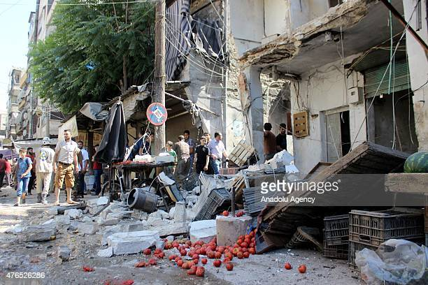 Syrians inspect rubble of buildings at a bazaar after a helicopter belonging to the Syrian Army bombed a residential areas in the Firdevs region of...