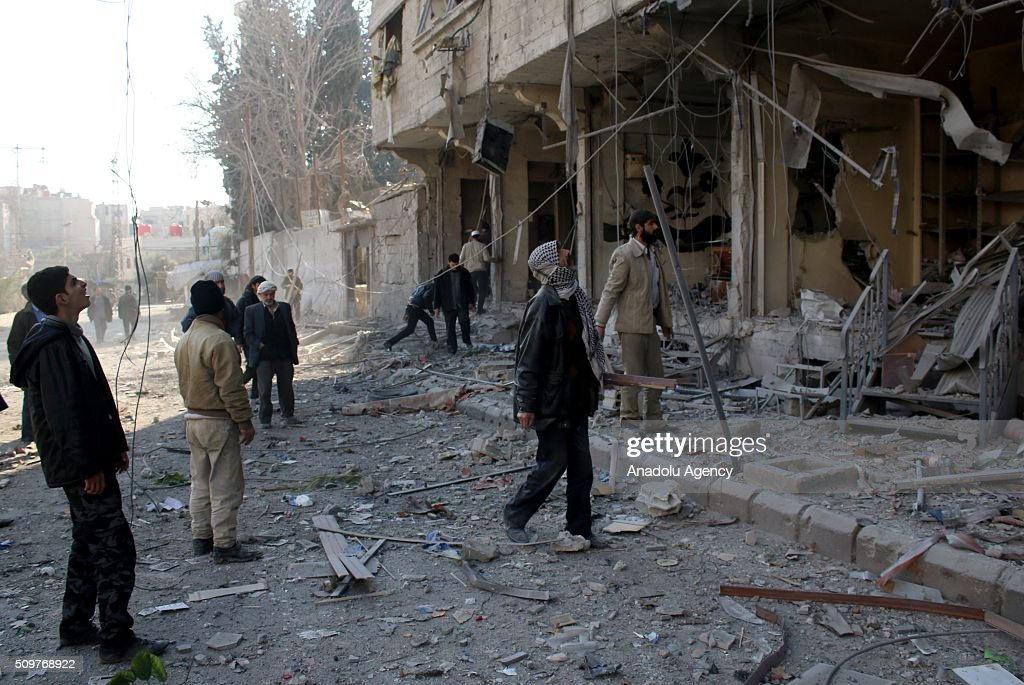 Syrians inspect the area after Assad regime war crafts carried out an airstrike over Eastern Ghouta region in Damascus, Syria on February 12, 2016.