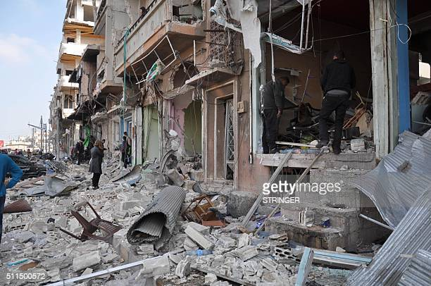 Syrians inspect the damage at the site of a double car bomb attack in the AlZahraa neighborhood of the central Syrian city of Homs on February 21...