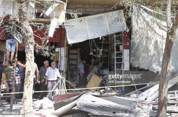 Syrians inspect the damage at the site of a suicide bomb attack in the capital Damascus' eastern Tahrir Square district on July 2 2017 Syrian state...