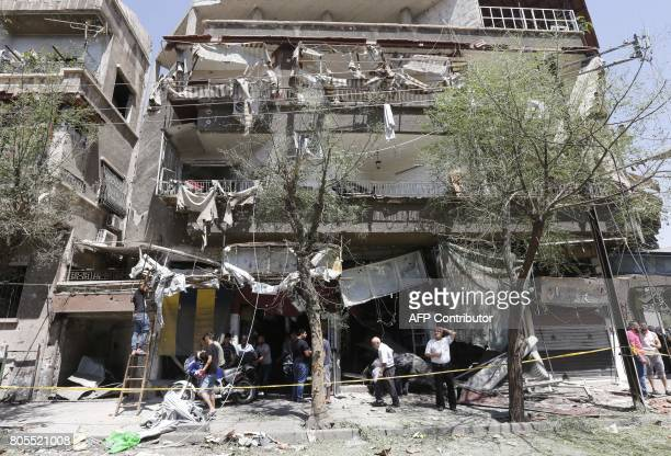 TOPSHOT Syrians inspect the damage at the site of a suicide bomb attack in the capital Damascus' eastern Tahrir Square district on July 2 2017 Syrian...