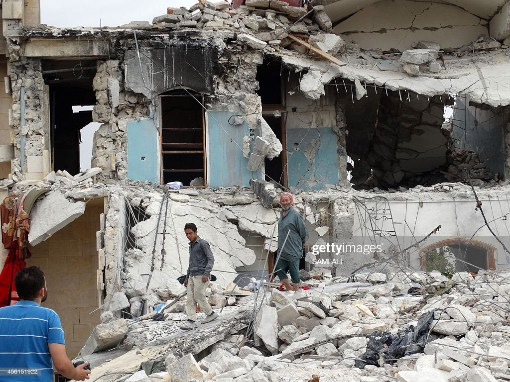 Syrians inspect the damage following a reported USled coalition air strike against the headquarters of alNusra Front 20 km west of the northern city...