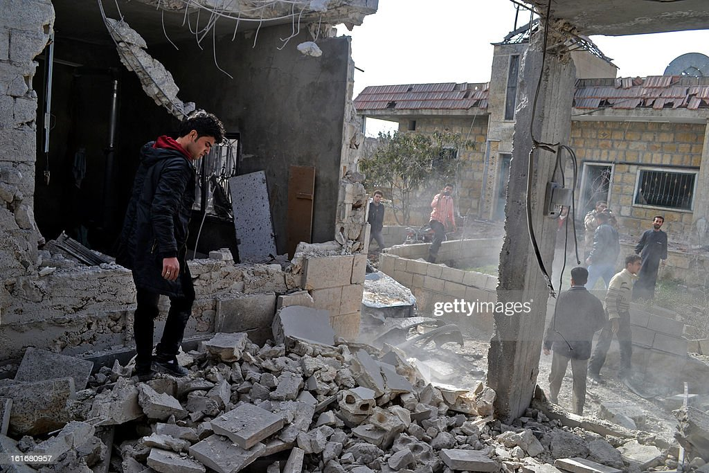 Syrians inspect the damage following an airstrike on the town of Hass, west of Maarat al-Numan, in the northern province of Idlib, where more than 10 people were killed, including four children, on February 14, 2013. As prospects faded for a political solution to the war that has killed nearly 70,000, UN chief Ban Ki-moon called on the Security Council to overcome its paralysis and take 'meaningful' action to stop the bloodshed.